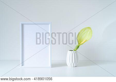 Empty White Frame Mockup On White Table. Modern White Vase With Arum Italicum Flower. Modern And Min
