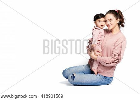 Side View Of Mother With Smiling Baby Daughter Looking At Camera Isolated On White Studio Background