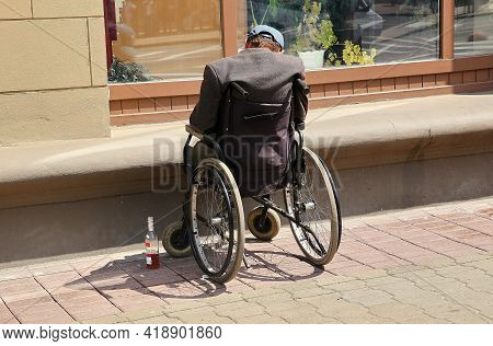 On The Street, A Disabled Person Is Sleeping In A Wheelchair After Drinking Alcohol.