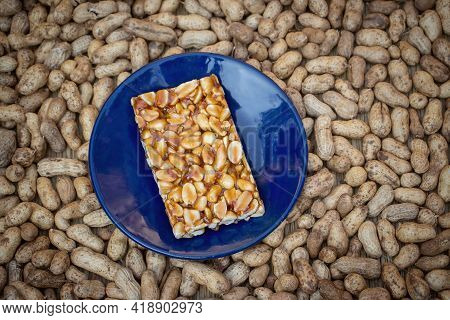 Peanut Chikki Or Jaggery Peanut Brittle Sweets In A Blue Plate Isolated On Peanut Pods