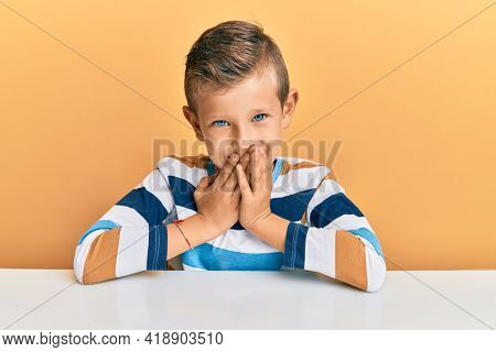 Adorable caucasian kid wearing casual clothes sitting on the table laughing and embarrassed giggle covering mouth with hands, gossip and scandal concept