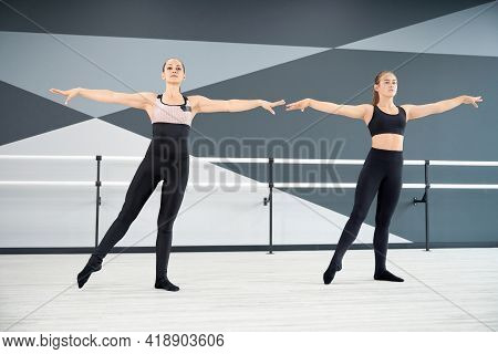 Adult Female Instructor Helping Young Girl In Black Sportswear Learn Choreographic Move. Two Synchro