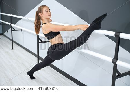 Flexible Female Teenager Wearing Tight Black Sports Outfit Practicing Split In Empty Dance Hall With