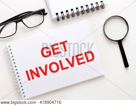 Get Involved Is Written In A White Notebook On A Light Background Near The Notebook, Black-framed Gl
