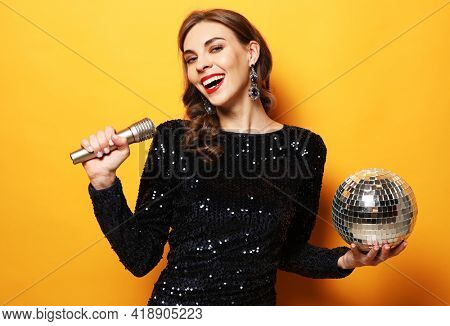 Young brunette woman with long curly hair dressed in evening dress holding a microphone and disco ball