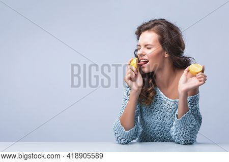 Cute Brunette Woman Holding Two Halves Of Yellow Lemon Citrus Fruit In Hands And Biting Wth Appetite