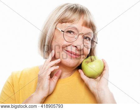 Food, health and old people concept: Portrait of senior woman holding an apple by her mouth