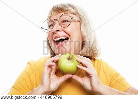 Food, health and old people concept: Portrait of senior woman wearing yellow shirt and glasses holding a green apple