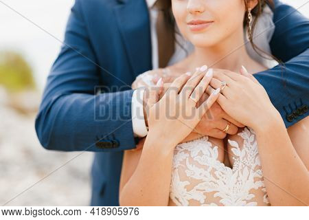 The Groom Gently Hugs The Bride By The Shoulders, The Bride Put Her Hands On The Grooms Arms, Close-