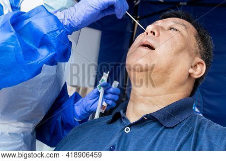 Mature Asian Man Doing Covid 19 Pcr Nasal Swab Test Via Nostril