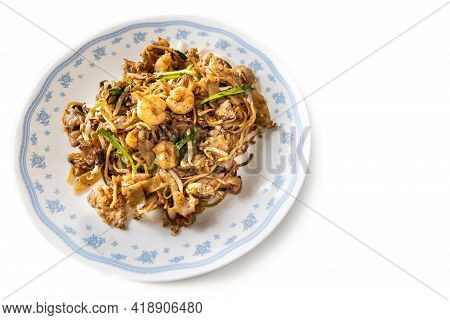 Overhead View Of Penang Char Kuey Teow Is Popular Fried Noodle With Coceral, Shrimp And Eggs In Blac