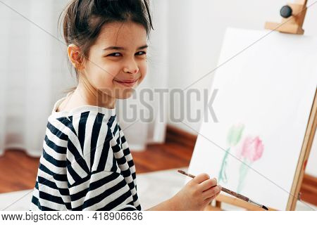 Candid Portrait Of A Little Girl Kid Smiling, Looking At The Camera, And Painting On The Paper On An