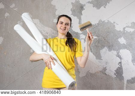 A Woman In A Bright Yellow T-shirt Holds 2 Rolls Of White Wallpaper Against The Old Wall. Repair Wor
