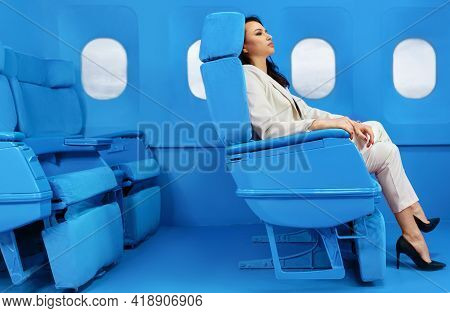 Businesswoman In A White Suit Sitting Near Windows At The First Class On The Airplane During Flight.