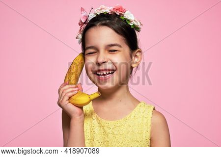 A Candid Portrait Of A Joyful Smiling Little Girl Holds A Banana, Like A Phone, Isolated On Pink Bac