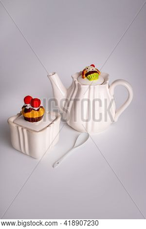 White Ceramic Teapot With Sweets Decor. Sugar Bowl With A Cupcake. Cake On The Teapot Lid. Ceramic T