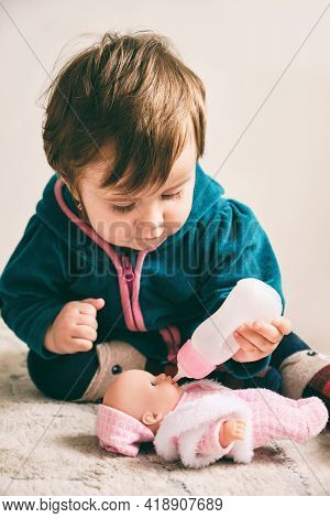 Baby Girl Playing With A Doll, Feeding A Doll From A Bottle, Taking Care Of A Doll. Life Style And C