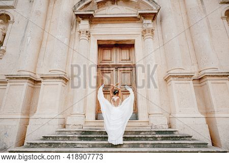 The Bride Threw Her Arms Over Her Head, The Skirt Flutters Around Her On The Ancient Stairs Of The T