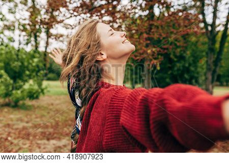 Horizontal Image Of A Authentic Young Woman Smiling With Arms Wide Open Posing On Nature Background.