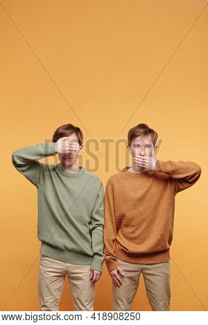One tween brother in sweater covering eyes while other brother covering mouth against orange background
