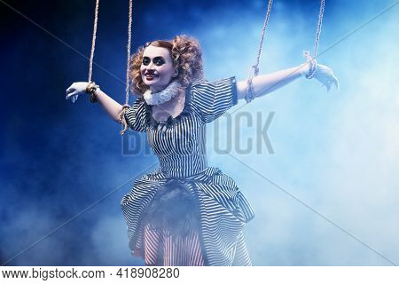 The actress plays a doll on strings at a performance in a puppet theater. A portrait in retro style.