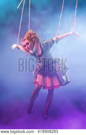 Puppet theater and circus. The actress plays a doll on strings at a performance in a puppet theater. Full length portrait in vintage style.