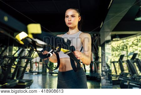 Horizontal Front View Of A Fit Woman Training With Trx Straps In The Gym. Sporty Female Exercising H