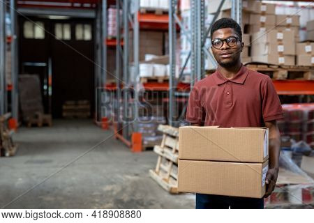 Portrait of smiling young African-American warehouse mover in eyeglasses standing with stack of boxes at stockroom with metal frame