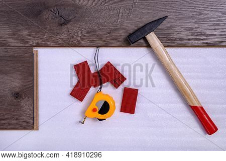 Equipment Or Tools To Install Laminate Floor. Hammer,  Spacers And Tape Measure On The Laminate Floo