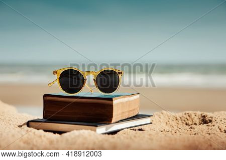 Reading Book Outdoor In Summer Concept. Book And Sunglasses On The Beach Sand In Front Of The Sea On