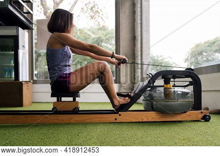Sportswoman Training His Strength In The Gym With A Water Rowing Machine, Active And Sporty Lifestyl