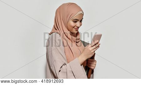 Cheerful Young Arabian Girl Student In Hijab Using Smartphone While Posing On Light Background, Wide