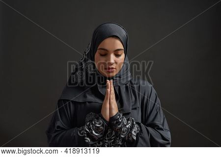 Young Arabian Girl In Traditional Hijab Praying With Closed Eyes While Posing On Dark Background. Be