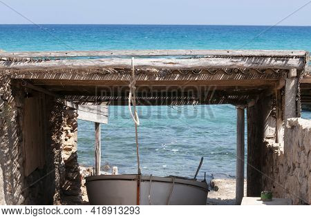 A Small Boat On Rails In The Rocky Beach. Boats On The Characteristic Wooden Rails On The Island Of
