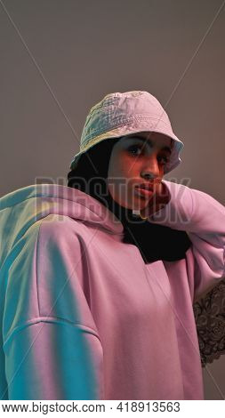 Portrait Of Cute Young Arabian Girl In Hijab And Panama Posing On Light Background And Looking At Ca