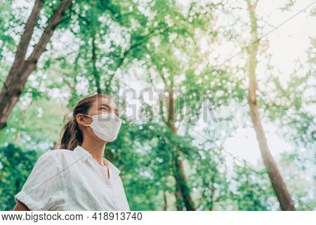Mask wearing woman looking up to bright future in hope walking in forest. Sustainable fashion fabric in PPE, asian girl lifestyle breathing clean air.