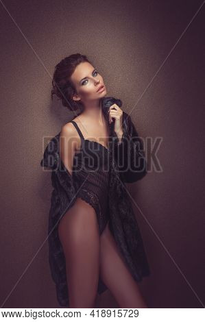 Beautiful Sexy Long-haired Brunette Woman In Black Lingerie And Fur Coat Posing In The Studio. The B
