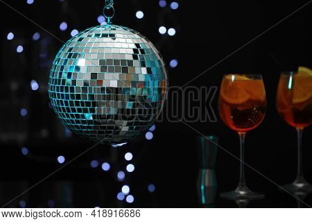 Shiny Disco Ball Hanging Over Bar Counter With Cocktails In Nightclub, Space For Text