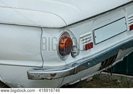 One Round Old Red Headlight On A White Retro Car Near A Gray Iron Rear Bumper