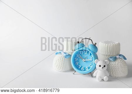 Alarm Clock, Toy Bear And Baby Booties On White Background, Space For Text. Time To Give Birth