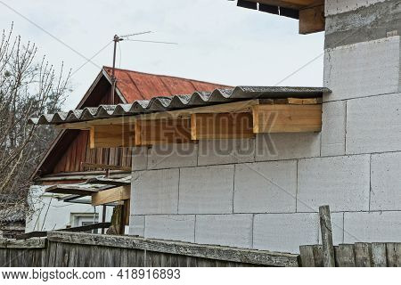 A Row Of Brown Wooden Planks Of Formwork Under A Gray Slate Roof On A White Brick Wall
