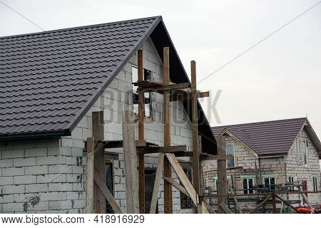 Part Of A Private Unfinished House Of White Bricks With Windows Under A Brown Tiled Roof Against A G