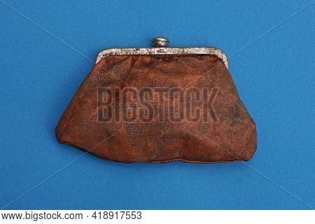 One Large Old Closed Brown Leather Wallet Lies On A Blue Table