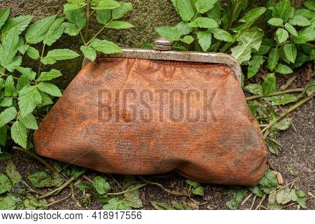 One Old Large Brown Leather Wallet Stands On The Ground In The Street Among Green Vegetation