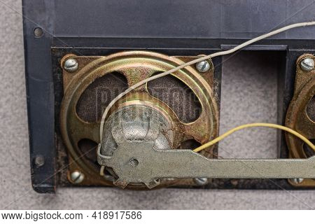One Small Old Metal Speaker With Wires On A Black Plastic Panel Lie On A Gray Table