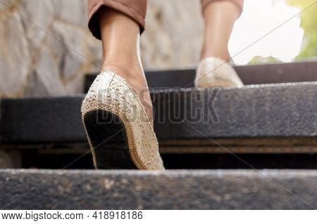 The Adult Woman Walking Up The Stairs.