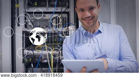 Graphic of world in center connected with bubbles, over caucasian man standing next to server rack. global technology, data processing and digital interface concept digitally generated image.