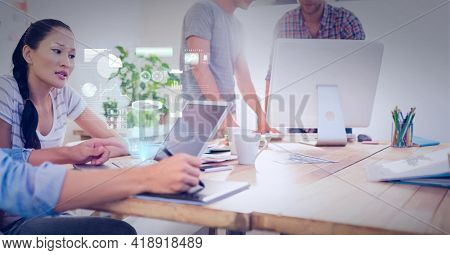 Composition of screen with data processing over business people in office using tablet and computer. global technology, data processing and digital interface concept digitally generated image.