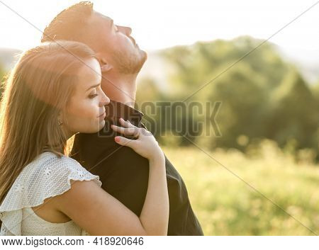 Couple lovers hugging and kissing in the park at sunset. Love, youth, happiness concept.