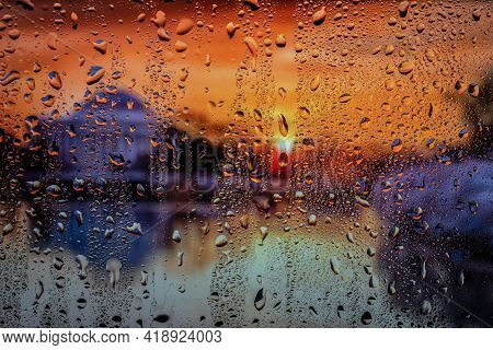 Raindrop On The Window, Backgorund Is Bluried A Light Of City. City Life In Night In Rainy Season Ab